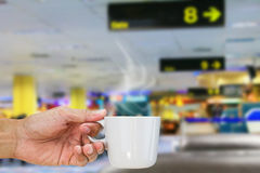 Hand holding hot coffee cup on blurred departure lounge in airport Stock Photo