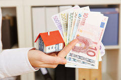 Hand holding house and Euro money stock photography