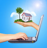 Hand holding house on green grass with tree, solar. Hand holding house on green grass with tree, wind turbine and solar panels of screen laptop. Hands typing on stock image