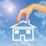 Hand holding house icon. Background of sky, clouds Stock Image