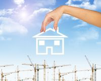 Hand holding house icon. Background of sky, clouds Royalty Free Stock Images