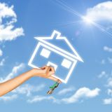 Hand holding house icon and key. Background of sky Stock Photo