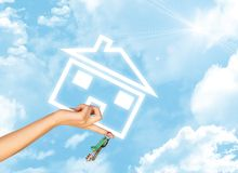 Hand holding house icon and key. Background of sky Stock Photography
