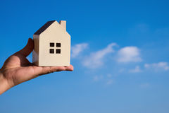 Hand holding a house model and a blue sky Stock Image