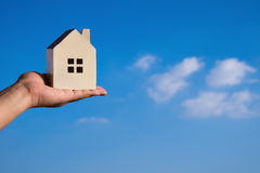 Hand holding a house model and a blue sky Royalty Free Stock Photo