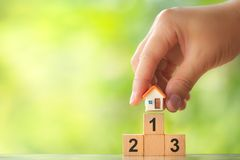 Hand holding house model on first place of winner podium on greenery blurred background stock photo