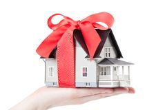 Hand holding house model with red bow Royalty Free Stock Photos
