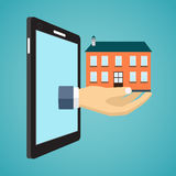 Hand holding house from screen of smartphone. Royalty Free Stock Image