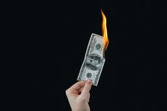 Hand holding hundred dollar bill on fire Royalty Free Stock Photo