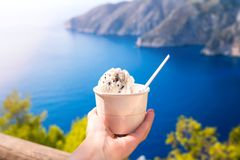 Hand holding ice cream agains blue sea stock images