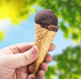 Hand holding ice cream with chocolate Royalty Free Stock Photography