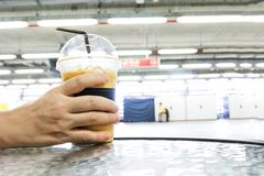 Hand holding Iced Coffee in Plastic Cup on table.  royalty free stock images