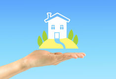 Hand holding an icon of a house with a lawn Stock Image