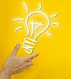 Hand holding idea. Light bulb on yellow background Stock Photos