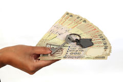 Hand holding Indian currency with house shape key Royalty Free Stock Photo