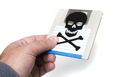 Infected computer floppy disk. Hand holding a infected computer floppy disk isolated on a white background. Conceptual image with skull and bones Stock Photography