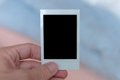 Hand Holding Instant Film. A man's hand holding an instant film print filled with a solid black space to customize with your own picture Royalty Free Stock Image