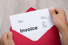 Hand holding invoice in envelope Stock Images