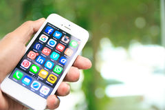 Hand holding iPhone with social media applications on screen Stock Image