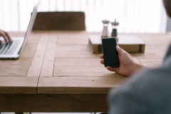 Hand Holding iPhone on Wooden Table Stock Photography