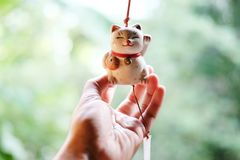 Hand is holding a Japan lucky cat doll is hanging on the windowWoman hand is holding a Japan lucky cat doll is hanging on th. Woman hand is holding a Japan lucky stock photos
