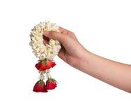 Hand holding jasmine garland on white background Stock Photo