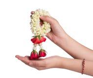 Hand holding a jasmine garland on white background Stock Photos