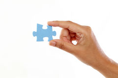 Hand holding jigsaw piece against white background. Hand holding jigsaw puzzle piece against white background Royalty Free Stock Images