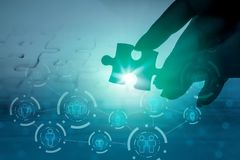 Hand holding jigsaw piece with background of teamwork people. Connection ,support ,unity Stock Images