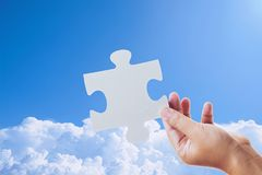 Hand holding a jigsaw puzzle and sky. Background Royalty Free Stock Photo