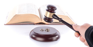 Hand holding a judge gavel above wedding rings Stock Image