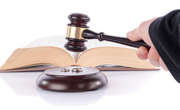 Hand holding a judge gavel above wedding rings Royalty Free Stock Images