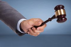 Hand holding judge mallet. Over blue background Stock Photos