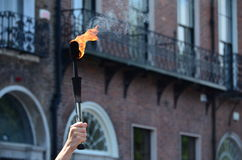 Hand holding a Juggling Fire Torch. A Hand holding high a Juggling Fire Torch Royalty Free Stock Image