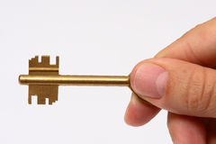 Hand holding a key. Of success over a white background Royalty Free Stock Photos