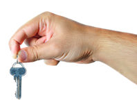 Hand holding a key. A man's hand holding a key with isolated white background Royalty Free Stock Image