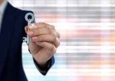 Hand holding key with bright ridged blurry background. Digital composite of Hand holding key with bright ridged blurry background Royalty Free Stock Image