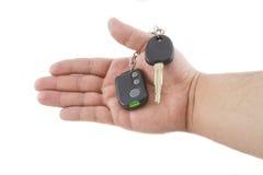 Hand holding key and car alarm system. Isolated on white background Stock Photo