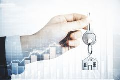 Mortgage and sales concept. Hand holding key on city background with abstract business chart. Mortgage and sales concept. Double expoure royalty free stock photos