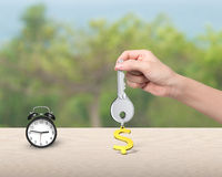 Hand holding key with dollar sign keyring and alarm clock Stock Photos