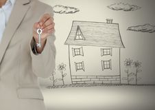 Hand Holding key with house drawing in front of vignette Stock Images