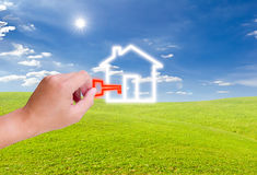 Hand holding key for house icon. On green grass meadow Stock Photography