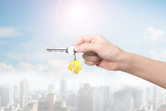 Hand holding key with house shape key-ring,3D rendering. Hand holding key with house shape key-ring, city background in sunny day,3D rendering Stock Images