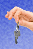 Hand holding key over blue sky Royalty Free Stock Image