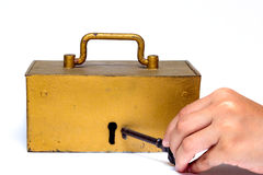 Hand holding key and treasure trunk. Isolated on a white background Stock Images