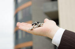 Hand holding keys. Office building in the background Royalty Free Stock Images