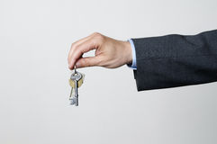 Hand holding keys. A man in a suit hands over the keys Royalty Free Stock Photography