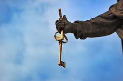 Hand holding keys of the kingdom of Heaven. Fragment of Statue of Saint Peter the Apostle: hand holding keys of the kingdom of Heaven against cloudy blue sky Stock Photos