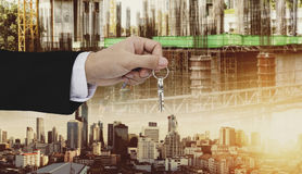 Hand holding keys, with site construction and city in sunset background Royalty Free Stock Photo