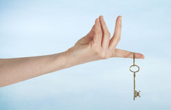 Hand with keys on sky background Royalty Free Stock Photo